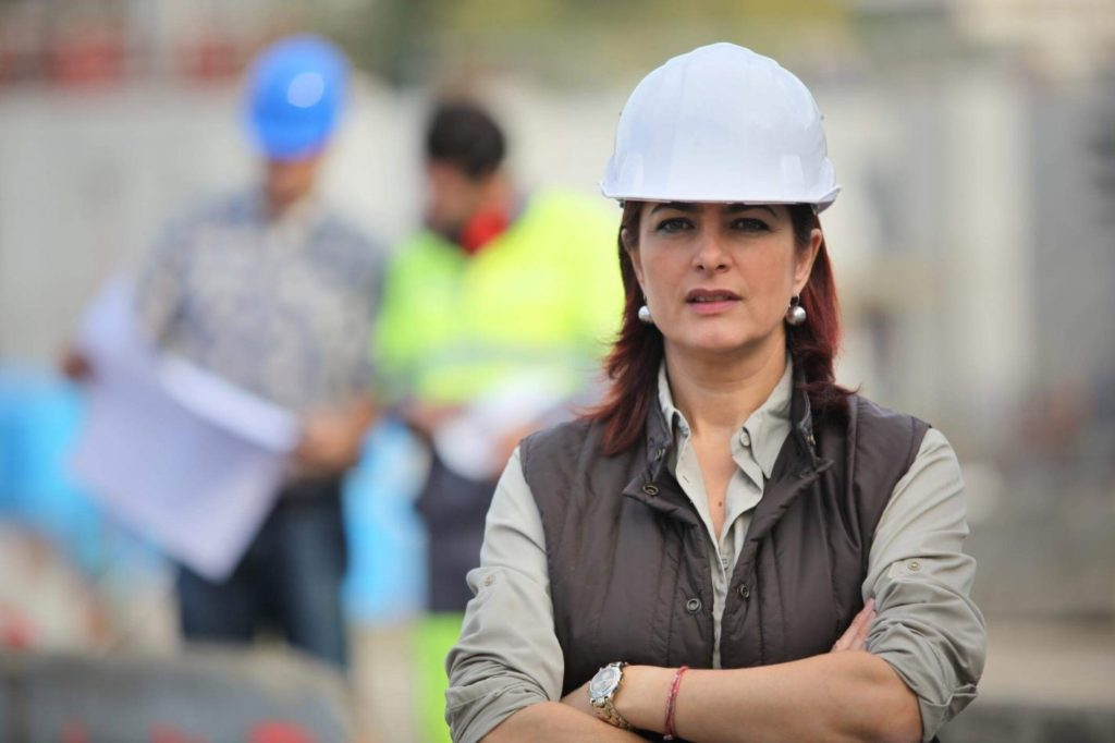 Female project manager in front of a building site with arms crossed