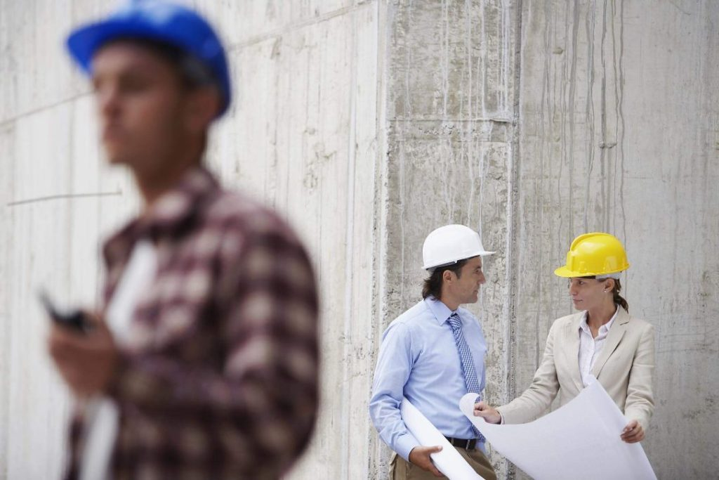 Two engineers discussing a commercial renovation job in front of the concrete wall of a building