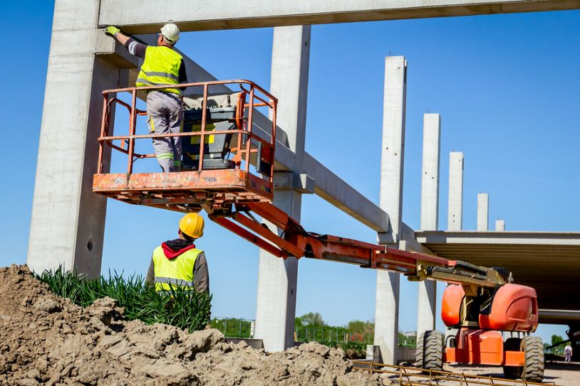 Construction worker uses a small mobile crane to inspect concrete poles for a large ground up development project.