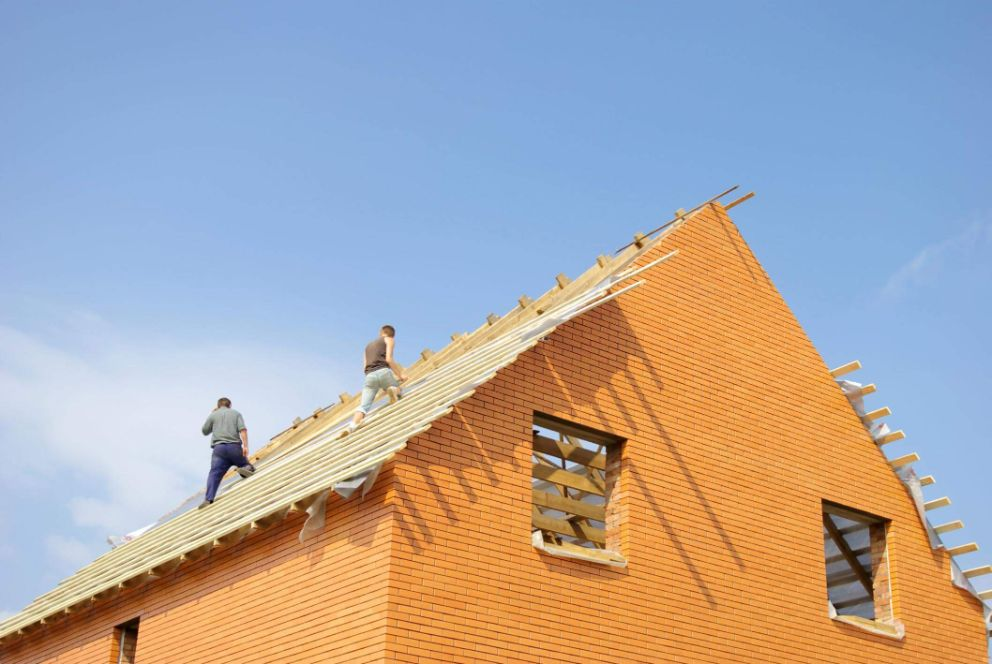 Workers installing a roof on a real estate investment